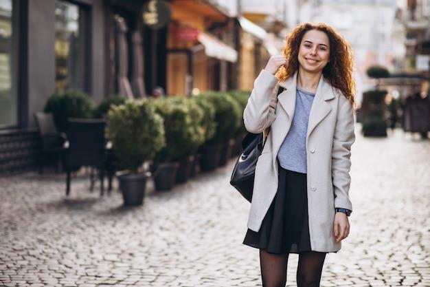 Jolie femme aux cheveux bouclés marchant dans une rue de café
