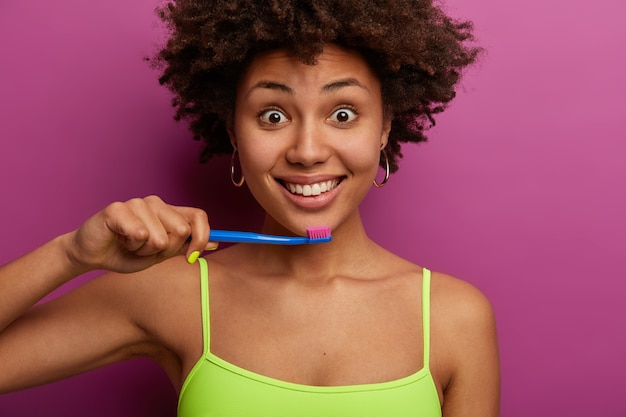 Jolie femme aux cheveux bouclés a un sourire sain à pleines dents, tient une brosse à dents