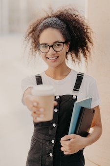 Jolie femme aux cheveux bouclés, tient du café à emporter, boit pendant la pause à l'université