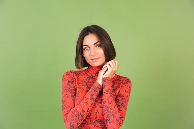 Jolie femme aux cheveux courts avec des boucles d'oreilles dorées légères, un chemisier imprimé de dragon de chine rouge sur des émotions positives vertes, un sourire confiant