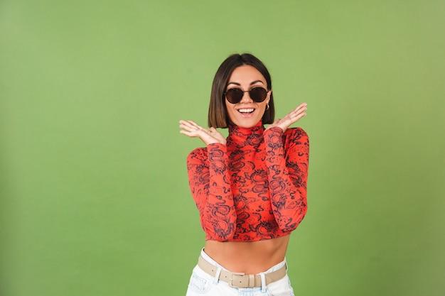 Jolie femme aux cheveux courts avec boucles d'oreilles dorées, lunettes de soleil, chemisier imprimé dragon de chine rouge sur vert