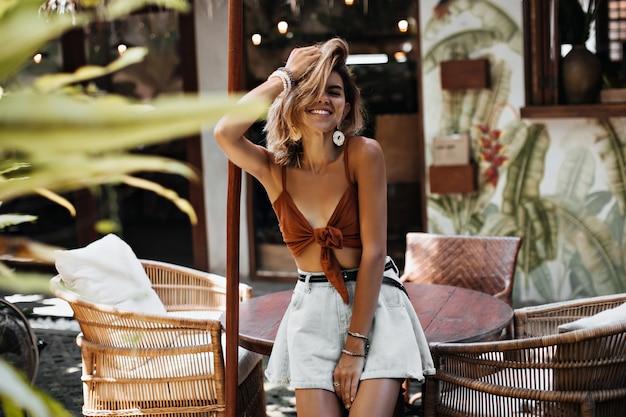 Jolie femme aux cheveux courts en soutien-gorge marron et chemises bleu clair rit dans une atmosphère chaleureuse à l'extérieur
