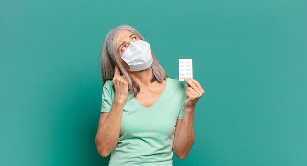Jolie femme aux cheveux gris avec un masque de protection et des pilules