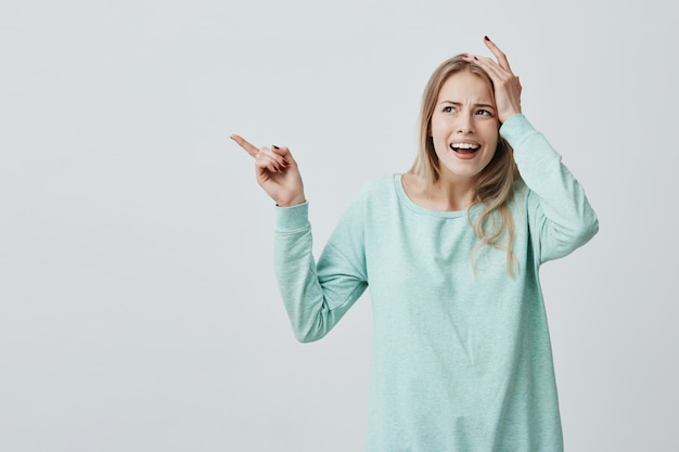 Jolie femme aux cheveux longs blonds tenant la main sur la tête comme si elle avait oublié quelque chose d'important, pointant l'index sur le côté