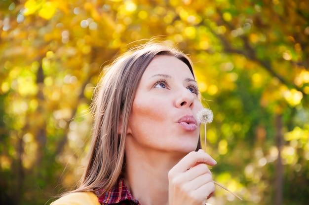 Jolie femme aux cheveux longs dans le parc soufflant un pissenlit