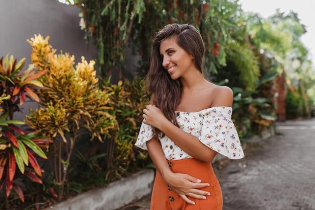 Jolie femme aux cheveux longs en jupe brillante et chemisier léger posant dans un jardin tropical