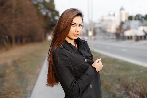 Jolie femme aux cheveux longs marchant au printemps