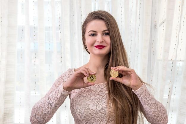 Jolie femme aux cheveux longs montrant deux bitcoins dorés
