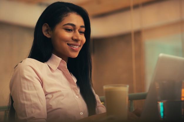Une jolie femme aux cheveux noirs a l'air confiante et heureuse tout en étant assise seule et en regardant l'écran de son ordinateur portable