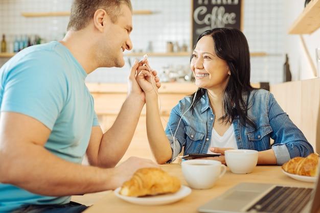 Jolie femme aux cheveux noirs joyeuse et un bel homme blond souriant assis à la table dans un café et écouter de la musique et prendre un café