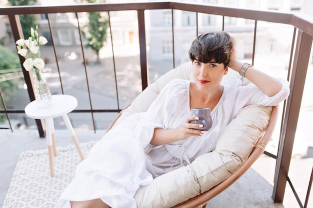 Jolie femme aux cheveux noirs en robe blanche à la recherche avec intérêt tenant une tasse de thé sur le balcon