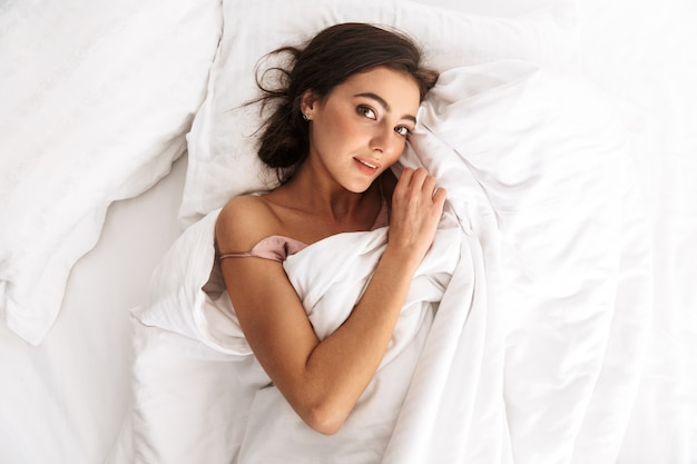 Jolie femme aux cheveux noirs souriant, en position couchée et en dormant dans son lit sur du linge blanc