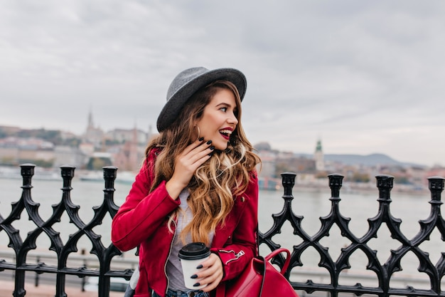 Jolie femme aux cheveux ondulés debout au pont et regardant la rivière en journée nuageuse
