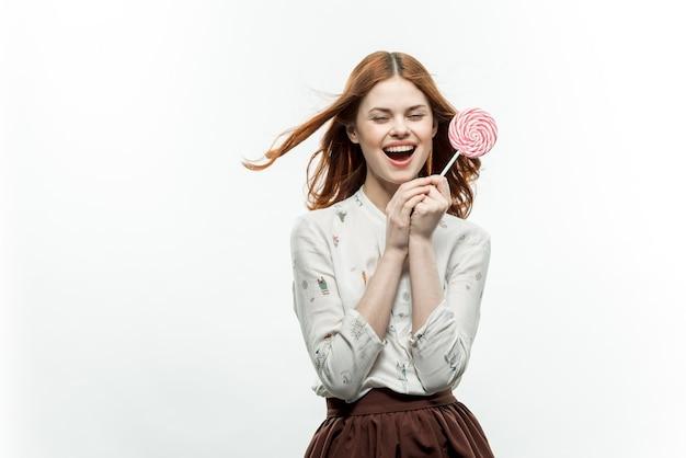 Jolie femme aux cheveux rouges entre les mains d'émotions de bonbons