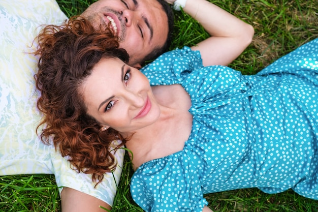 Jolie femme aux cheveux rouges en robe bleue et jeune homme allongé sur l'herbe