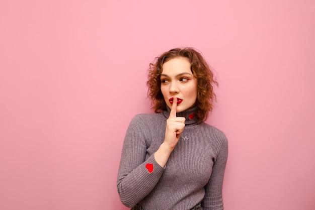 Jolie femme aux cheveux roux bouclés a mis son doigt sur ses lèvres, montre un geste de silence