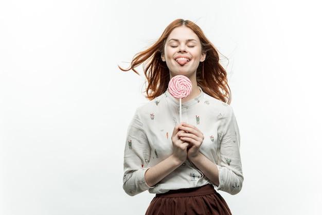 Jolie femme aux cheveux roux ronde lollipop fun émotions lumière