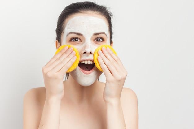Jolie femme aux épaules nues appliquant les soins de la peau de maquillage