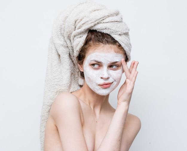 Jolie femme aux épaules nues charme masque visage peau claire vue recadrée.