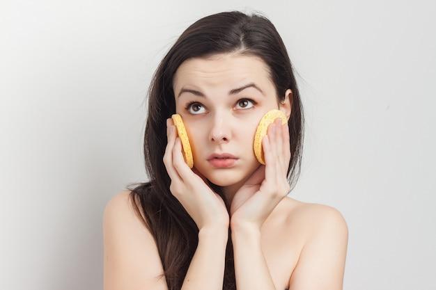 Jolie femme aux épaules nues essuie son visage avec des éponges. photo de haute qualité