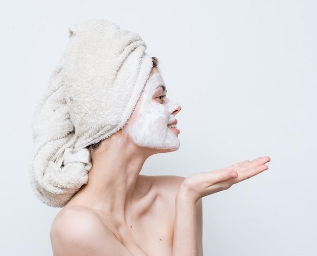 Jolie femme aux épaules nues face à une serviette crème sur la peau propre de la tête.
