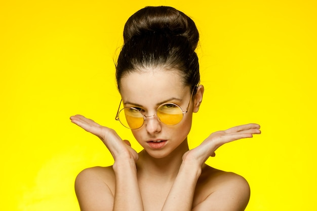 Jolie femme aux épaules nues portant des lunettes de cheveux rassemblés sourire fond jaune. photo de haute qualité