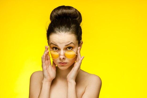 Jolie femme aux épaules nues rassemblé les cheveux peau claire fond jaune. photo de haute qualité
