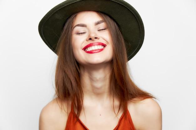 Jolie femme aux lèvres rouges posant contre le mur blanc