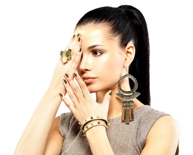 Jolie femme aux ongles dorés et beaux bijoux en or isolés sur blanc