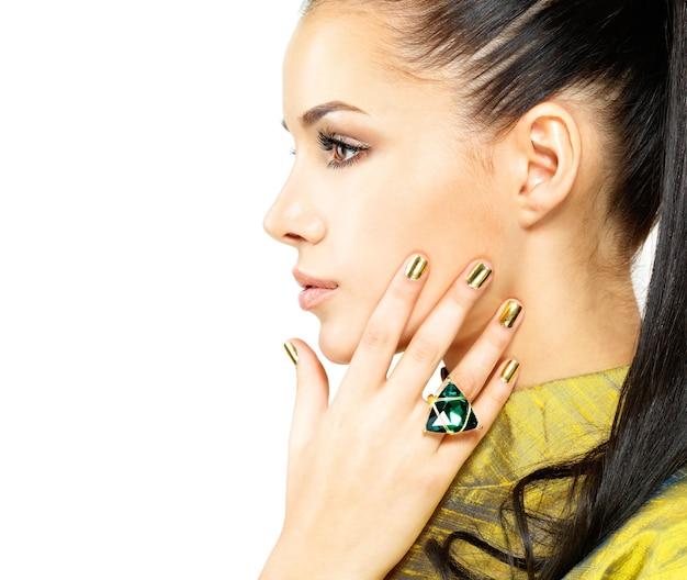 Jolie femme aux ongles dorés et belle émeraude en pierre précieuse