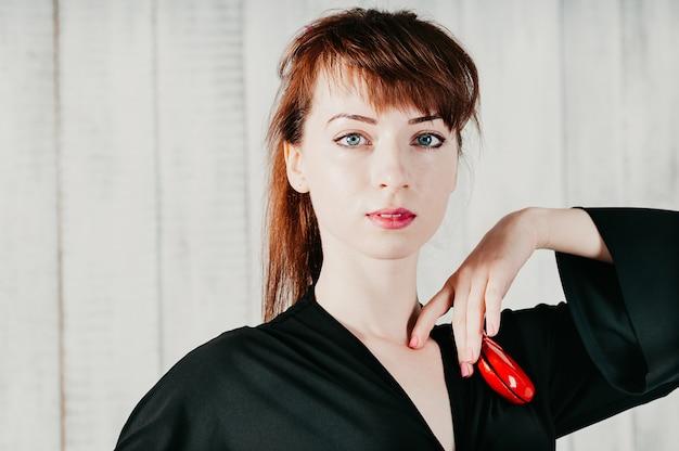 Jolie femme aux yeux bleus en robe noire, avec des castagnettes rouges, fond clair