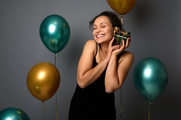 Jolie femme aux yeux fermés embrasse doucement son cadeau de noël, debout près de beaux ballons à air brillants de couleurs vertes métalliques et dorées, portrait isolé sur fond gris avec espace de copie pour l'annonce