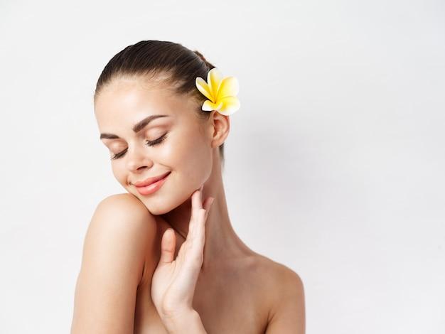 Jolie femme aux yeux fermés épaules nues fleur jaune dans les cheveux