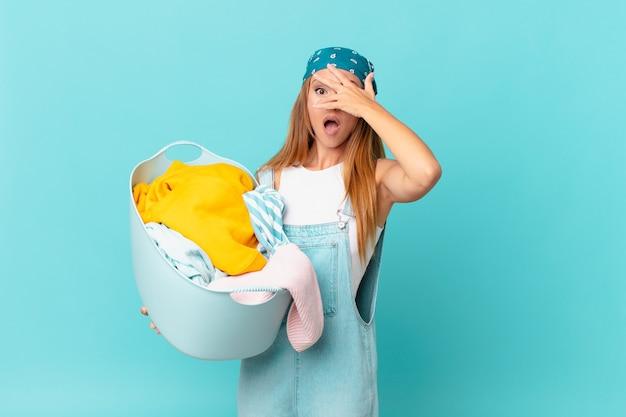 Jolie femme ayant l'air choquée, effrayée ou terrifiée, couvrant le visage avec une main tenant un panier de lavage