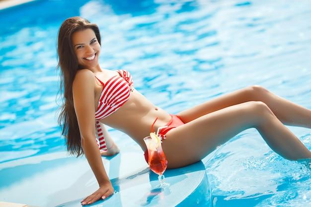 Jolie femme ayant un bronzage naturel près de la piscine.