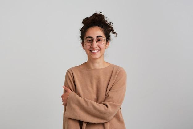 Jolie femme, belle fille aux cheveux bouclés foncés, portant un pull beige et des lunettes