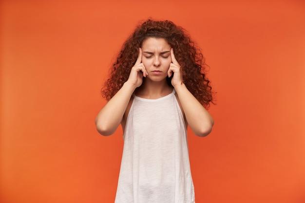 Jolie femme, belle fille aux cheveux bouclés roux. porter un chemisier blanc à épaules dénudées. garde les yeux fermés et masse les tempes, maux de tête. stand isolé sur mur orange