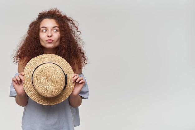 Jolie femme, belle fille aux cheveux bouclés roux. porter un chemisier rayé à épaules dénudées et un chapeau. faire une grimace. regarder vers la droite à l'espace de copie, isolé sur mur blanc