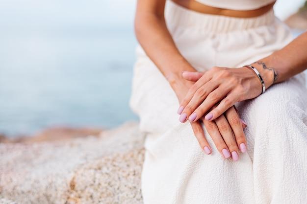 Jolie femme bien entretenue les mains sur les genoux