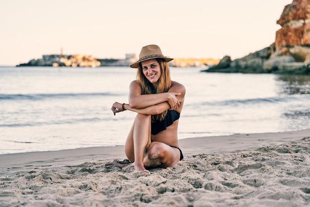 Jolie femme en bikini assis sur le sable à la plage.