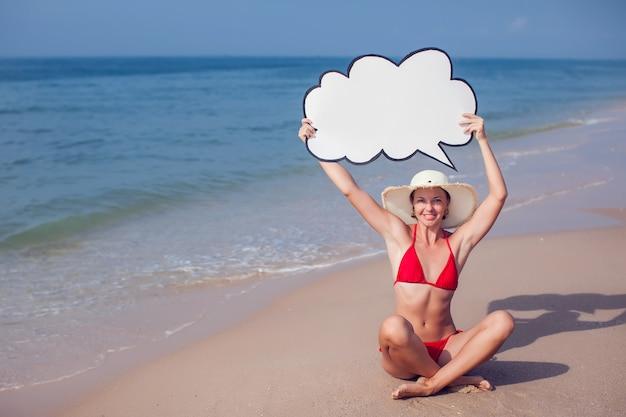 Jolie femme en bikini avec discours de bulle dans les mains sur la plage