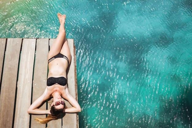 Jolie femme en bikini noir se faire bronzer allongé sur une jetée en bois