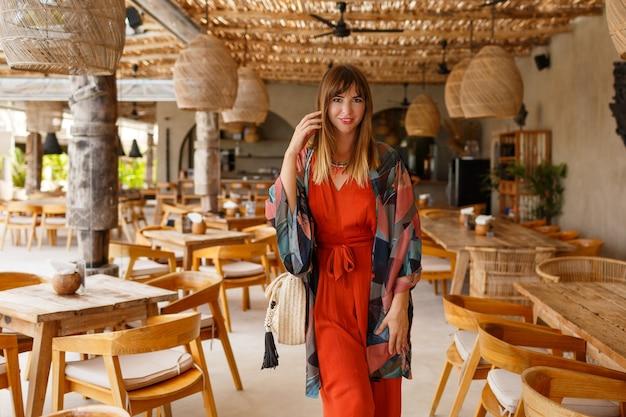 Jolie femme blanche en autfit bohème d'été élégant posant dans un café tropical.
