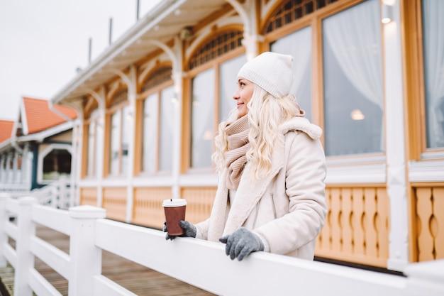 Jolie femme blonde d'âge moyen profiter du temps en plein air au jour d'hiver