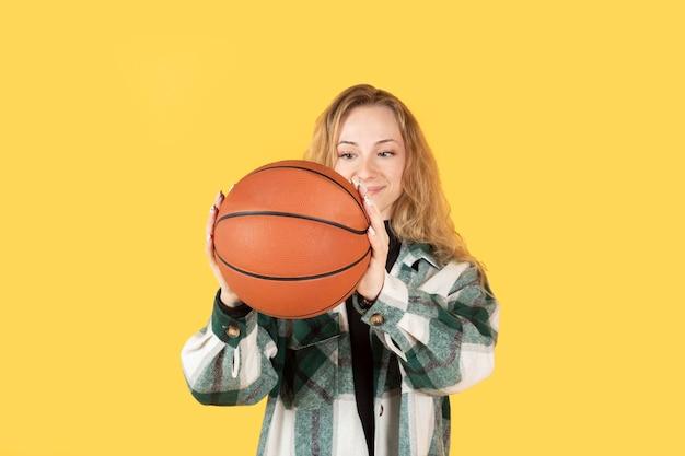 Jolie femme blonde à l'aide de ballon de basket, fond jaune