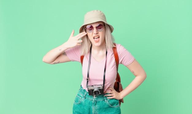 Jolie femme blonde à l'air malheureuse et stressée, geste de suicide faisant signe d'arme à feu. concept d'été