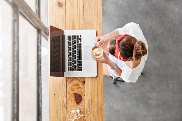 Jolie femme blonde assise dans la vue de dessus de café