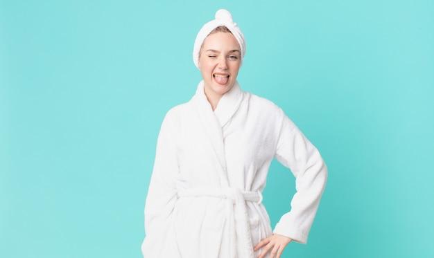 Jolie femme blonde avec une attitude joyeuse et rebelle, plaisantant et tirant la langue et portant un peignoir