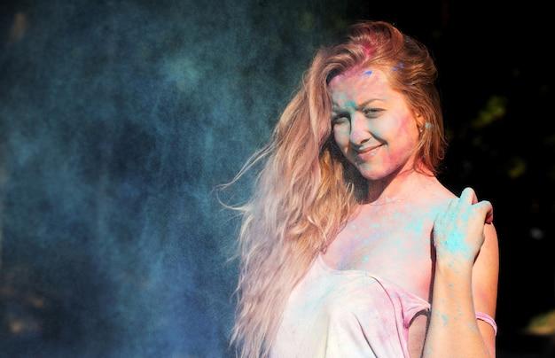 Jolie femme blonde aux cheveux bouclés posant dans un nuage de poudre bleue au festival des couleurs holi