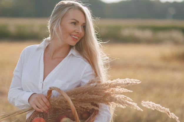 Une jolie femme blonde aux cheveux longs dans un champ au coucher du soleil porte une corbeille de fruits et un bouquet de paille. été, agriculture, nature et air pur à la campagne.